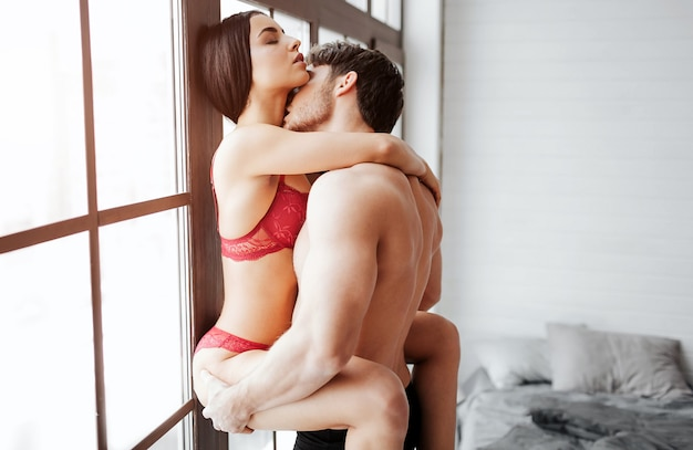 Passionate couple having sex at window. young woman in red lingerie embraces man with legs and hands. he hold her buttocks and kiss in neck.