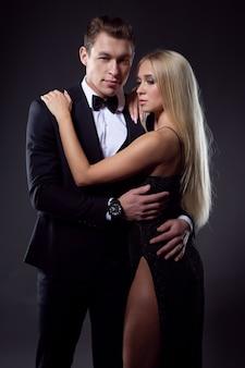 사랑에 열정적 인 커플 : 검은 드레스에 가벼운 헤어 스타일을 가진 여자와 정장 포즈의 아름다운 형태가 이루어지지 않은 남자 프리미엄 사진