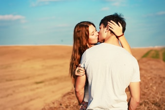 Passionate couple kissing in the meadow