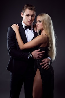 Passionate couple in love: a woman with a light hairstyle in a black dress and a beautiful unshaven man in a suit pose