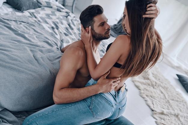 情熱的なカップル。家で時間を過ごしている間結合している美しい若い半服を着たカップルの上面図