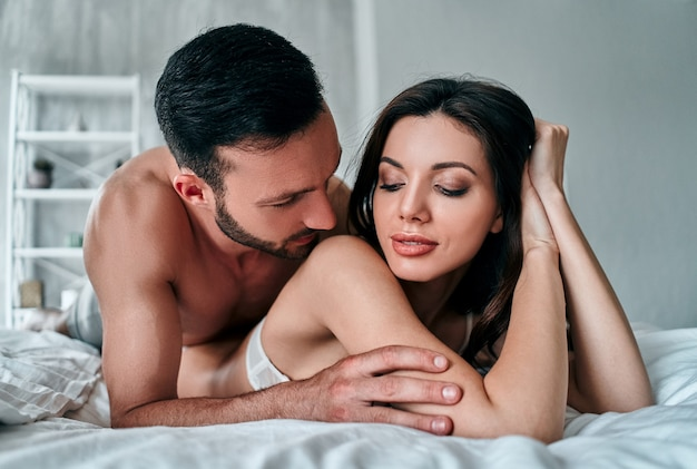 The passionate couple in underwear laying in the bed