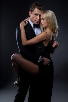 Passionate couple: a woman with a light hairstyle in a black evening dress and a handsome man in a suit with a bow tie pose in a dark studio