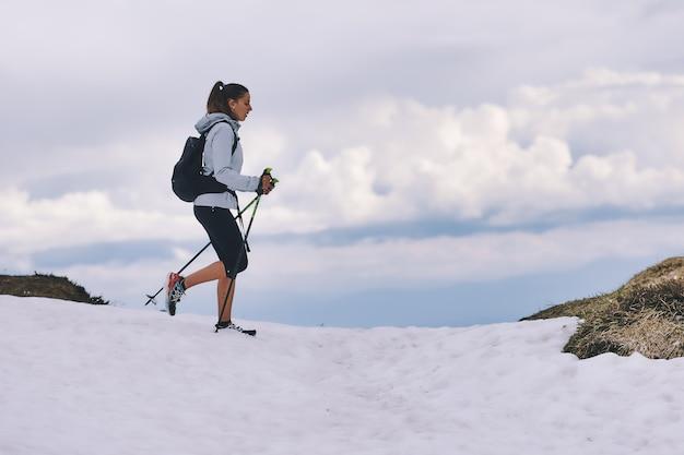 눈 위를 걷는 동안 야외 스포츠의 열정적 인 소녀