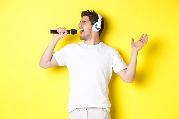 Passionate guy in headphones holding microphone, singing karaoke song, standing over yellow background in white clothes.