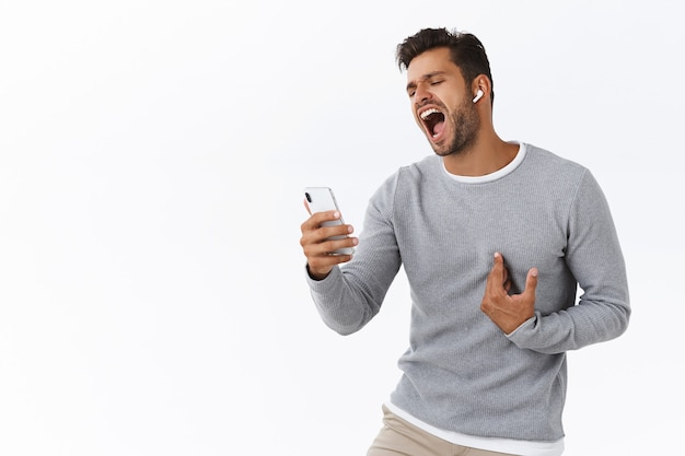 Passionate handsome caucasian guy with bristle enjoy and relaxing after work with mobile karaoke game or app, holding smartphone, listens to music in wireless earphones, singing along, white wall
