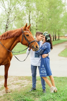 Passionate hug of a couple in love who look at each other and the guy holds a horse for a bridle
