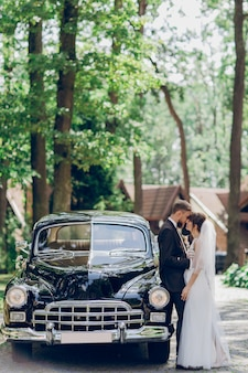 Passionate kiss of newlyweds standing behind old black retro car