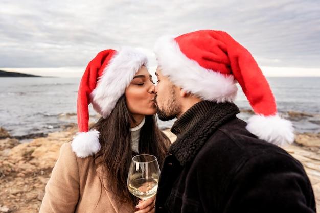 겨울 바다 크리스마스와 새해 휴가에 바다 바위에 연인 커플의 열정적 인 키스