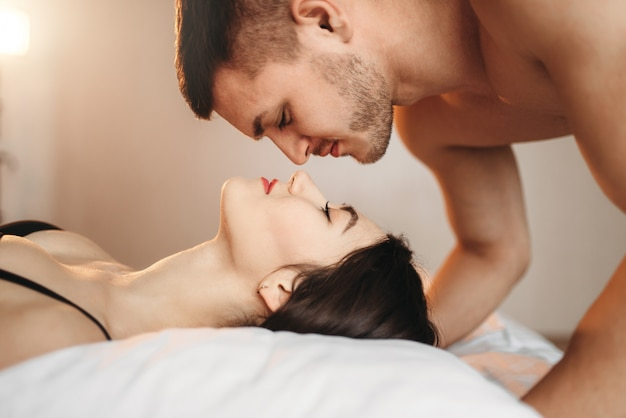 열정적 인 사랑 부부는 큰 흰색 침대, 섹스 로맨스에 놓여 있습니다. 침실, 친밀한 애호가, 에로틱 게임의 친밀한 커플