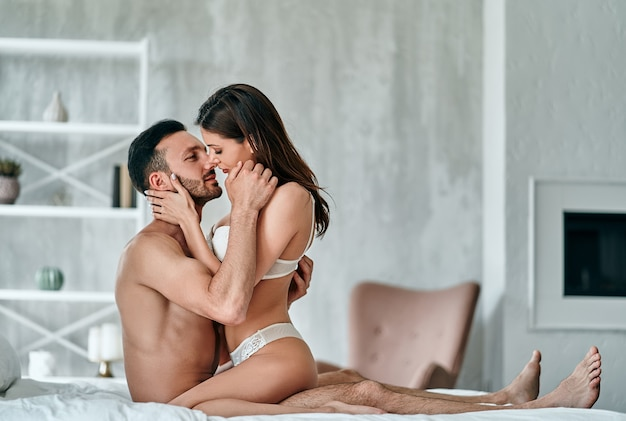 The passionate man and woman having sex in the bed