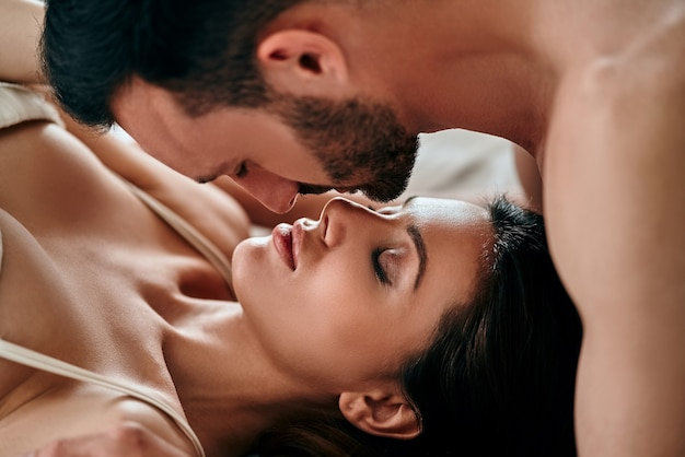 The passionate man and woman kissing in the bed