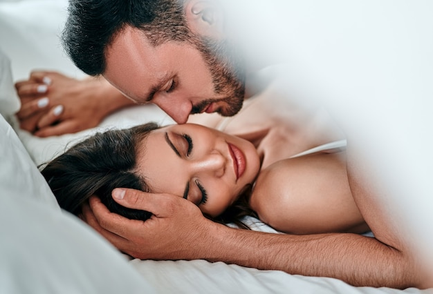 The passionate man and woman playing in the bed