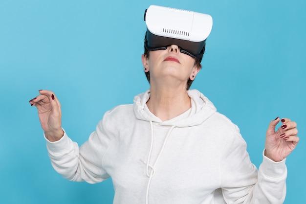 스웨터를 입은 열정적 인 중년 여성이 적 청색 벽에 가상 현실 안경으로 새 영화를보고있다. 중년층을위한 첨단 기술 접근성의 개념.