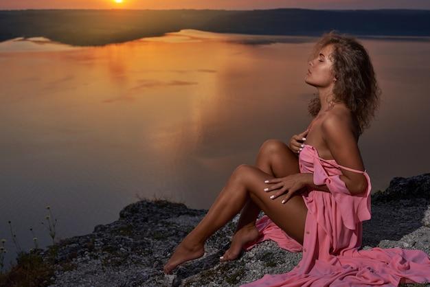 열정적 인 모델 포즈, 일몰의 배경에 앉아.