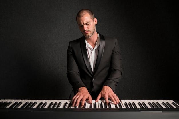 Страстный музыкант, играющий аккорды на фортепиано в студии