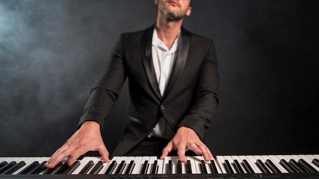 ピアノで和音を演奏する情熱的なミュージシャン