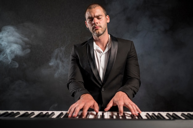 Passionate musician playing chords on piano smoke effect