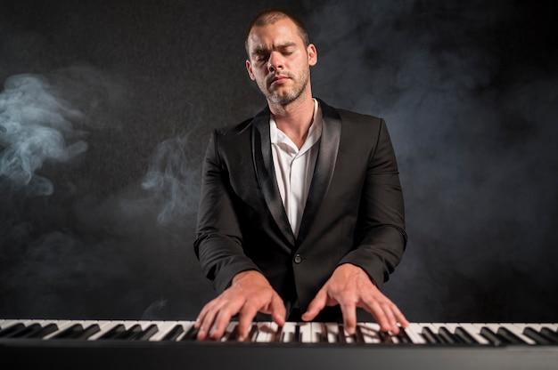 Musicista appassionato che suona accordi sull'effetto fumo di pianoforte