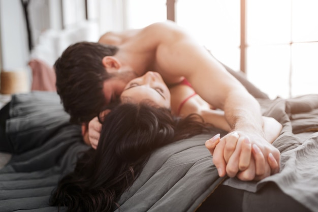 Passionate sexy young couple lying on bed in room. he is above and kisses model. couple hold hand in hand. they enjoy the moment.