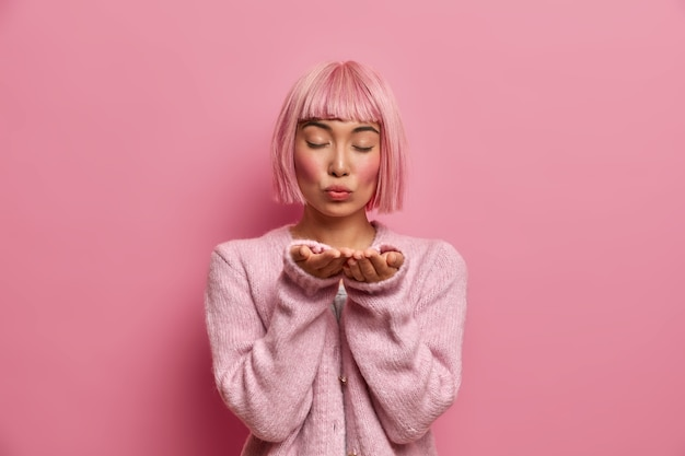 Passionate tender asian lady sends air kiss with folded lips, stands with eyes closed, has pink bob hairstyle, dressed in warm comfortable sweate