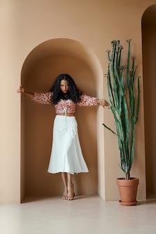 벽의 틈새에 서 있는 트렌디한 옷을 입은 열정적인 여성