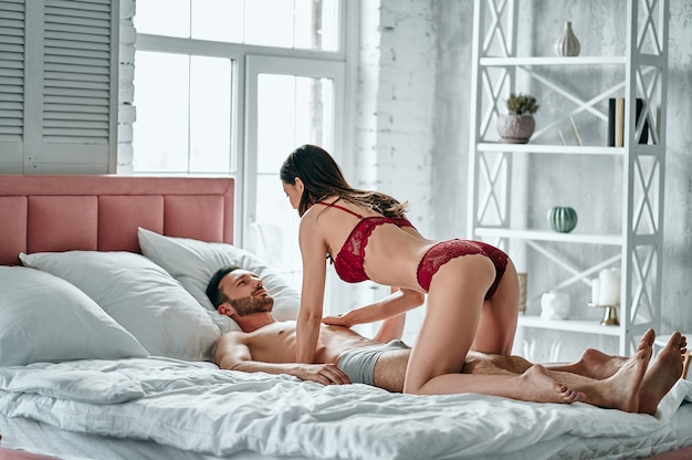 The passionate woman and man playing in the bed