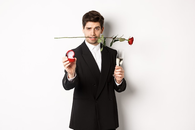 Passionate young man in suit making a proposal, holding rose in teeth and glass of champagne, showing engagement ring, asking to marry him, standing against white background