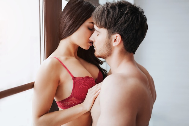 Passionate young woman in red lingerie stand at window and kiss with man. he leans to her. model touch her partner with hand.