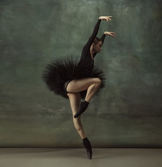 Passioned. graceful classic ballerina dancing, posing isolated on dark studio wall