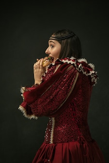 Passioned. portrait of medieval young woman in red vintage clothing eating burger on dark background. female model as a duchess, royal person. concept of comparison of eras, modern, fashion, beauty.