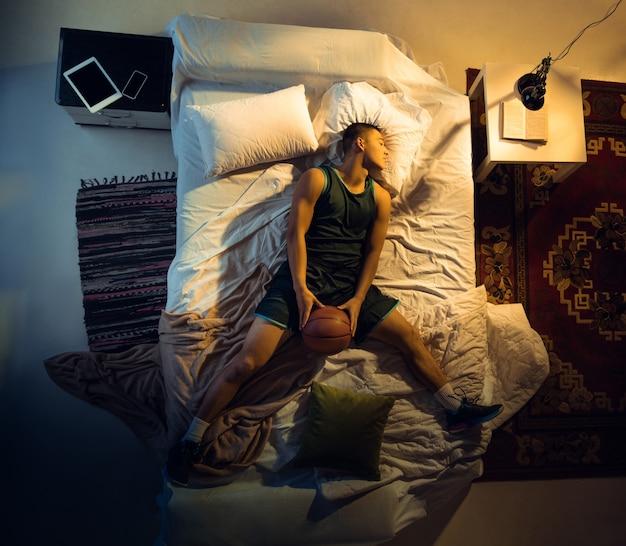 Страстный вид сверху молодого профессионального баскетболиста, спящего в своей спальне