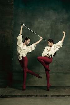 情熱的。濃い緑の壁に剣を持ったデュエリストのような2人の若い女性バレエダンサー。一緒に踊る白人モデル。バレエとコンテンポラリー振り付けのコンセプト。