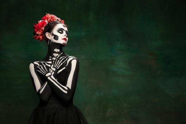 열정적이다. 산타 무에르테 세인트의 죽음이나 밝은 화장을 한 설탕 해골 같은 어린 소녀. copyspace와 어두운 녹색 스튜디오 배경에 고립 된 초상화. 할로윈 또는 죽은 자의 날을 기념합니다.