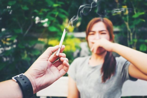 Концепция пассивного курения. человек курит сигарету, а женщина закрывает лицо, стоп смо