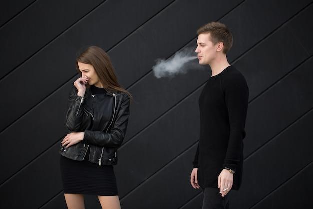 Концепция пассивного курения женщина закрывает лицо от сигаретного дыма