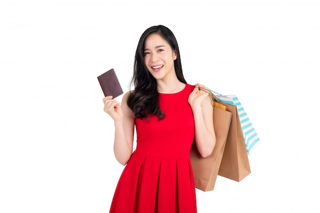 幸せなアジア女の買い物袋を保持していると別の手でpassortを示す
