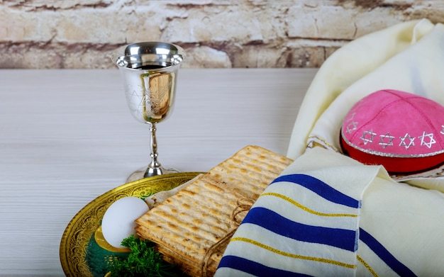 Passover background glasses wine and matzoh jewish holiday bread over wooden board.