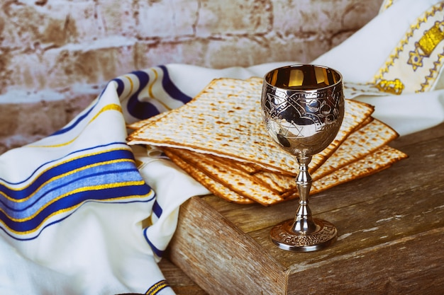 Passover background red wine and matzoh jewish holiday bread over wooden board .