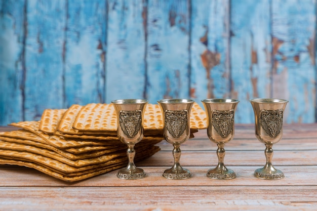Passover four glasses wine and matzoh jewish holiday bread over wooden board.
