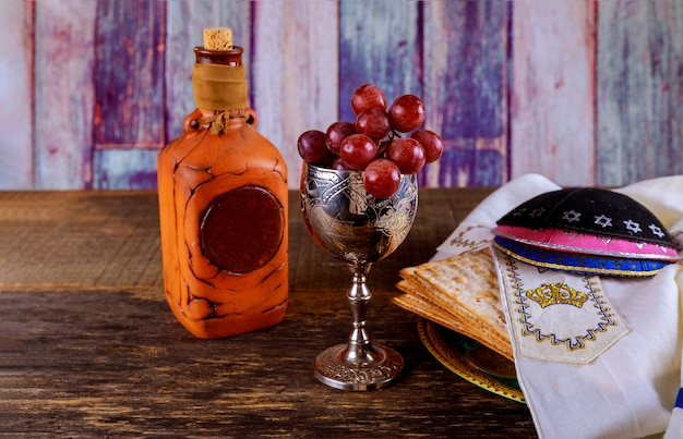 Passover glasses kosher wine and matzoh jewish holiday bread over wooden board.