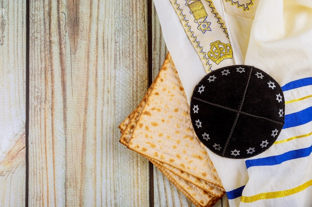 Passover matzoh jewish holiday bread kippah and tallit on wooden table.