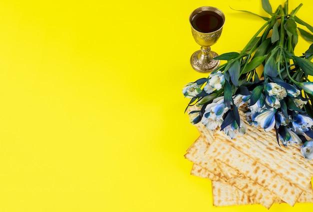 過越の祭りのシンボルマッツォ、赤ワインと花。ユダヤ教の祝日。