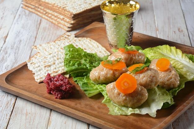 過越の伝統的なユダヤ人の食べ物-ニンジン、レタス、ホースラディッシュ、マツァーのゲフィルテ魚