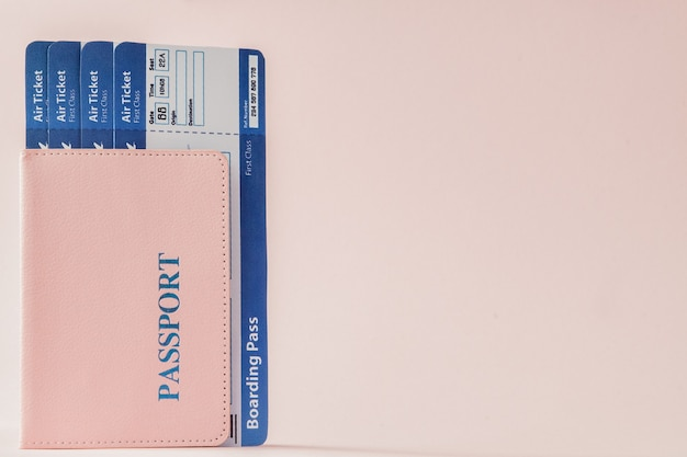 Passport and air ticket on a pink
