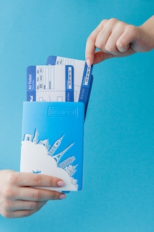 Passport and air ticket in woman hand on a blue background. travel concept, copy space