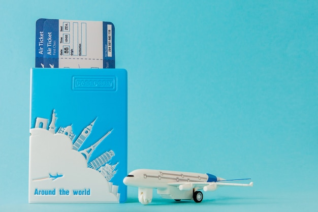 Passport, airplane and air ticket on a blue background. travel concept, copy space