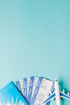 파란색 배경에 여권, 비행기 및 항공 티켓. 여행 개념, 복사 공간.