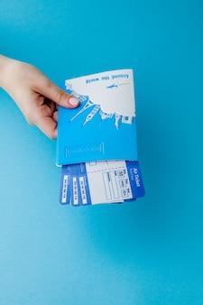 파란색 배경에 여자 손에 여권 및 항공권