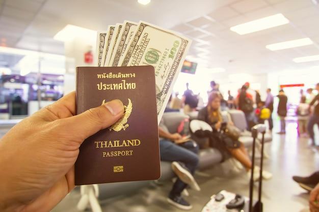 パスポートと空港に座っている男性の手でドル